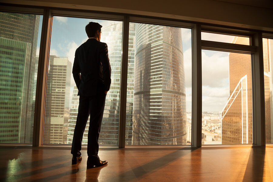 Man standing in an empty office looking at city outside.