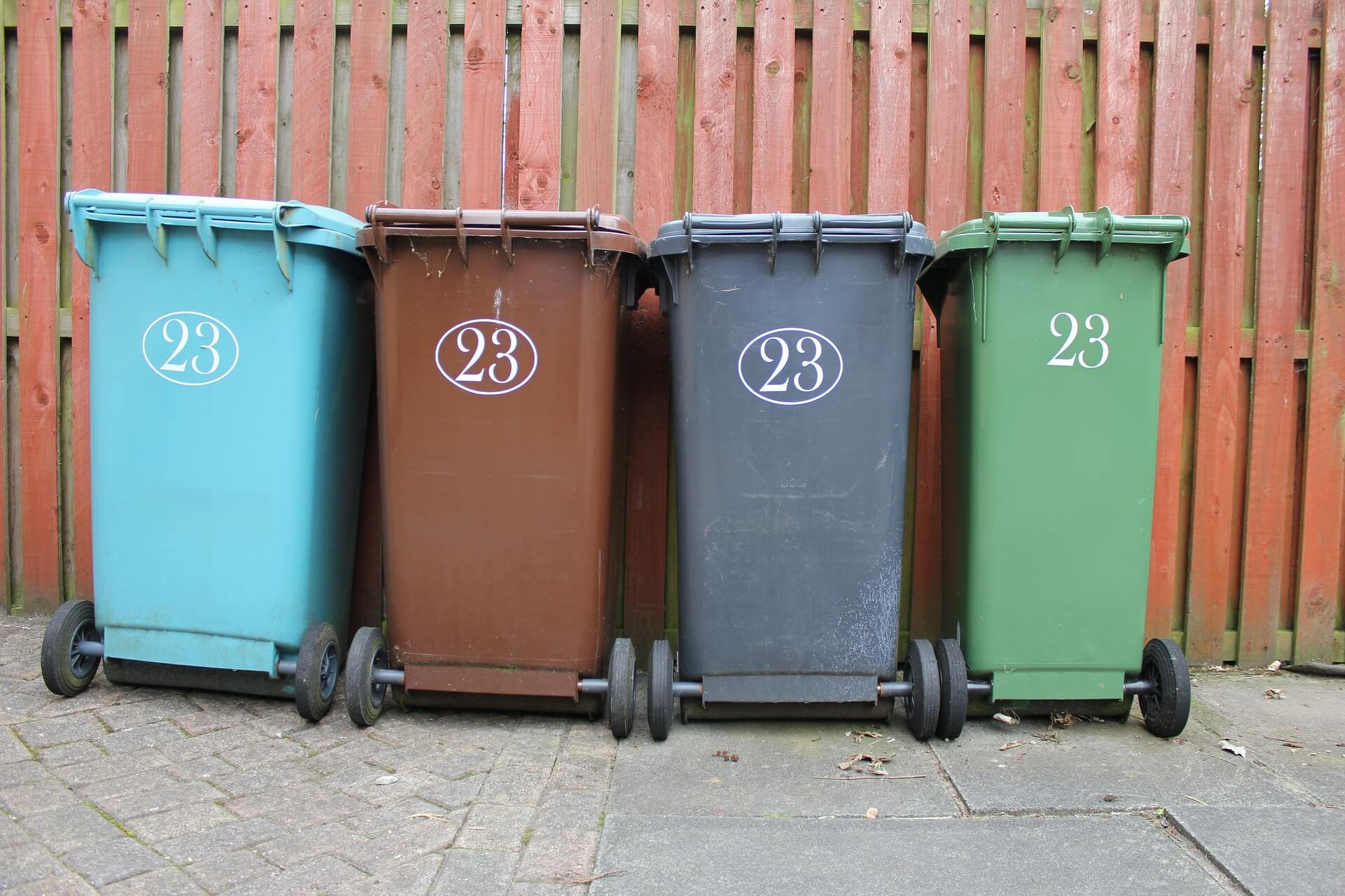 Four different colored trash cans with the number 23 on each of them.